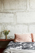 Bed with bedside table in front of concrete wall