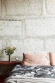Bett mit Nachtkasten vor Betonwand