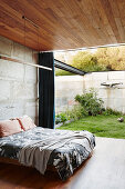 Double bed in the bedroom with concrete wall, wooden ceiling and terrace access
