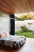 Doppelbett im Schlafzimmer mit Betonwand, Holzdecke und Terrassenzugang