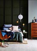 Bettwäsche im Patchwork-Stil auf dem Bett vor einer Kassettenwand