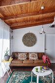 Braune Ledercouch und weißer Tisch im Wohnzimmer mit Holzbalkendecke