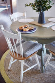 Round dining table with wooden chairs on carpet