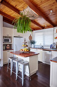 Breakfast counter with bar stools in white kitchen