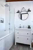 Waschtischmöbel neben Badewanne mit Duschwand in weiß gefliestem Badezimmer