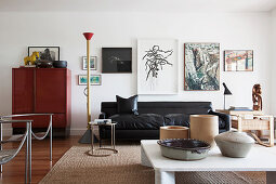 Black leather sofa below gallery of pictures in living room