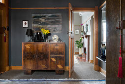 Black lamp and vases on Art Deco cabinet against black wall