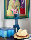 Straw hat, sculpture and striped box below painting