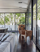 Sculptural chair in living room with glass walls