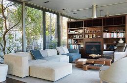 Wohnzimmer in Naturtönen mit Fensterfronten und Wohnwand