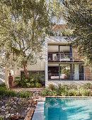 Blick vom Pool und dem Garten aufs Architektenhaus mit Balkonen