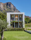 Cubic house with loggia and glass wall against mountain backdrop
