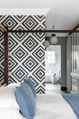 Four-poster bed in bedroom with black-and-white geometric wallpaper