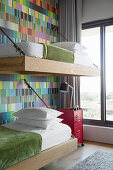 Bunk-beds suspended from wall decorated with colourful wallpaper
