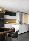 Black upholstered chairs at round table in front of open-plan kitchen