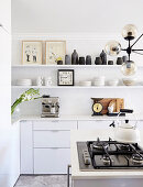 Shelves and gas hob on island counter in white kitchen