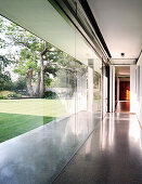 Corridor with glass wall overlooking garden with well-tended lawn