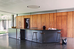 Island counter and fitted wooden cupboards in open-plan kitchen