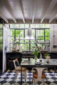 Gedeckter Tisch in schwarz-weißer Küche mit Fabrikfenster