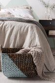 Diagonally painted basket with a knitted plaid in front of the bed