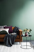 Brown sofa with pillows and plaid against an empty green wall