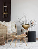 Wicker armchair and small side tables in natural shades in seating area