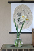 Narcissus in vintage vase in front of picture on torn newspaper