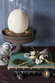 Vintage-style, Easter still-life arrangement with ostrich egg under glass cover