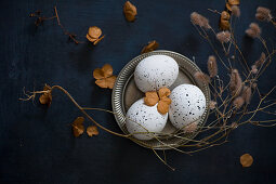 Dried flowers around speckled eggs on pewter plate