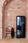 Vintage chair next to fridge in brick niche
