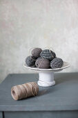 Easter eggs wrapped in fabric on cake stand and reel of twine
