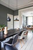 Langer Esstisch mit Klassikerstühlen im Esszimmer mit dunkler Wand und weißer Dielenboden
