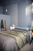 Double bed in bedroom with grey wall