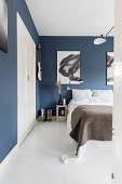 Double bed in bedroom with blue wallpaper, large artworks and white wooden floor