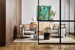 Blick auf Designer-Loungesessel und Coffeetable vor Sideboard, seitlich Einbauschrank