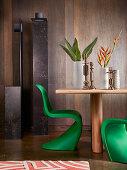 Designer-Stehleuchte, Holztisch mit Vasen und Kerzenhaltern und grüner Panton-Stuhl vor Wand mit dunkler Holzverkleidung