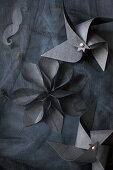 Windmills and flower made from black paper on black fabric