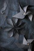 Windräder und Blume aus schwarzem Papier auf schwarzem Stoff