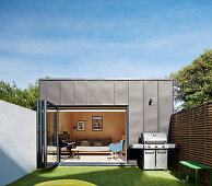 Separate accommodation block in garden with folding terrace door leading into bedroom
