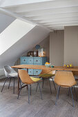 Shell chairs around narrow wooden table in attic interior