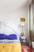 Colourful textiles in bedroom with Bohemian ambience