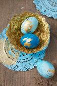 Ostereier und selbstgebastelte Pappmache-Schalen in Blau und Gold