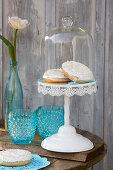Frühlingshafte Donuts auf blauer Tortenspitze unter Glasglocke