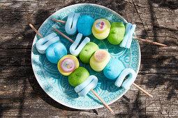Süsse Marshmallow-Spiesse auf Holztisch im Freien