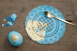 Osterei und Tortenspitze dekoriert in Blau und Gold