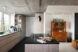 Moderne Küche mit grauen Fronten, Betondecke und altem Buffetschrank