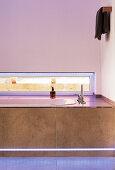 Bathtub with strip lighting below narrow horizontal window
