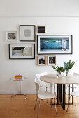 Runder Tisch mit Stühlen im Essbereich, gerahmte Fotos an der Wand