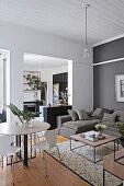 Wohnraum mit rundem Esstisch, grauem Polstersofa und Couchtischen
