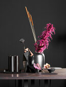 Black vase of pink Amaranthus on table in front of black wall